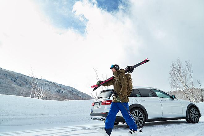E 220 d 4MATIC オールテレインをバックにスキー板を担ぐ河野さん